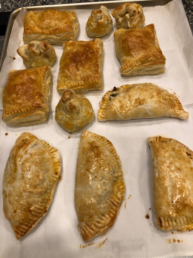 empanadas of all sizes and different crusts on a baking sheet