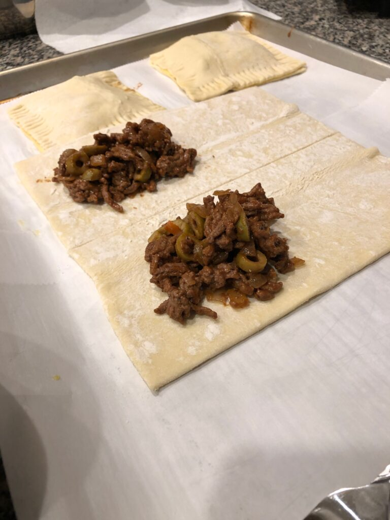 beef empanada filling on top of puff pastry before baking